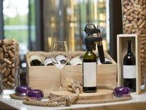Una botella de vino con un sacacorchos y un vidrio vacío en un tablón de madera, un interior del restaurante, en el fondo de a Fotos de archivo libres de regalías