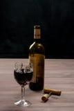 Una botella de vino con un vidrio, corcho y un sacacorchos Imagen de archivo libre de regalías