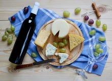 Una botella de vino, de queso y de uvas Imagenes de archivo