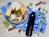 Una botella de vino, de queso y de uvas Foto de archivo