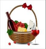 Una botella de vino, de uvas y de queso en una cesta de mimbre Fotos de archivo