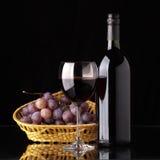Una botella de vino rojo, de vidrio y de uvas Fotografía de archivo