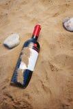 Una botella de vino rojo en la arena fotos de archivo
