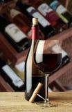 Una botella de vino y de un vidrio con un sacacorchos Fotografía de archivo libre de regalías