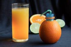 Una botella hecha de naranja natural con un tubo de consumición y un vidrio de zumo de naranja recientemente exprimido rodeado po imágenes de archivo libres de regalías