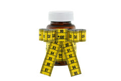 Una botella marrón de la medicina con la cinta métrica amarilla Fotografía de archivo