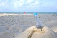 Una botella plástica de agua potable que deja en desorden en la playa de la arena con un fondo azul hermoso del mar fotografía de archivo