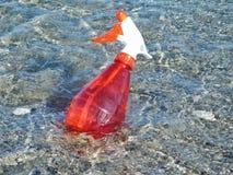 Una botella roja de la regadera en el mar Imágenes de archivo libres de regalías