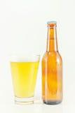 Una botella y un vidrio de cerveza aislados en blanco Fotos de archivo