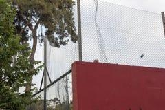 Una bottiglia della plastica e della corte murata rosso al recinto immagini stock