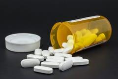 Una bottiglia delle pillole rovesciate su fondo nero Fotografia Stock Libera da Diritti