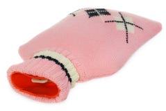 Una bottiglia di acqua calda in maglione rosa con i modelli bianchi e neri Immagini Stock