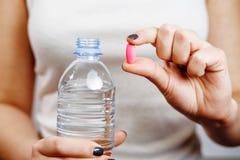 Una bottiglia di acqua in compressa della mano della donna fotografia stock