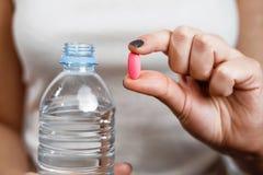 Una bottiglia di acqua in compressa della mano della donna in altra mano immagini stock