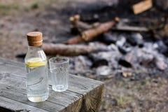 Una bottiglia di acqua con il limone e un vetro Falò estinto i fotografia stock