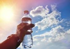 Una bottiglia di acqua in una mano contro il cielo ed il sole fotografia stock libera da diritti