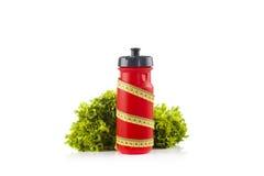 Una bottiglia di acqua rossa della bicicletta avvolta con nastro adesivo di misurazione giallo di plastica con lattuga verde nei  Fotografia Stock
