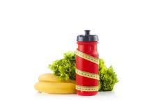 Una bottiglia di acqua rossa della bicicletta avvolta con nastro adesivo di misurazione giallo di plastica con lattuga verde nei  Immagini Stock