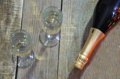 Una bottiglia di champagne e di vetri sui precedenti di un albero di Natale decorato con le luci del ` del nuovo anno e delle pal immagine stock