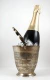 Una bottiglia di champagne in una benna di ghiaccio isolata Immagine Stock Libera da Diritti