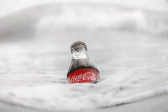 Una bottiglia di Coca-Cola nell'acqua ghiacciata Fotografia Stock