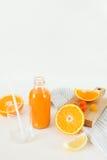 Una bottiglia di fresco arancio su una tavola bianca, accanto ad un vetro di fresco e delle arance con il limone Immagini Stock