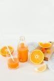 Una bottiglia di fresco arancio su una tavola bianca, accanto ad un vetro di fresco e delle arance con il limone Immagini Stock Libere da Diritti