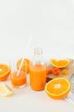 Una bottiglia di fresco arancio su una tavola bianca, accanto ad un vetro di fresco e delle arance con il limone Fotografie Stock