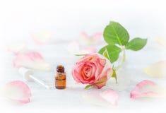 Una bottiglia di ml con olio essenziale, rosa fresco e petali, pipetta su bianco Fotografia Stock