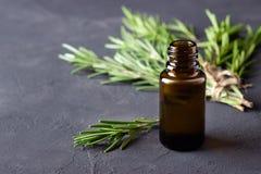 Una bottiglia di olio essenziale con i ramoscelli freschi dei rosmarini fotografie stock