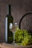 Una bottiglia di vino bianco, di un vetro di vino bianco su un fondo dell'uva e del barilotto sulla tavola di legno Immagine Stock