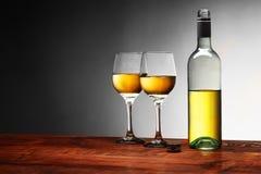 Una bottiglia di vino con due calici pieni fotografia stock libera da diritti