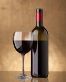 Una bottiglia di vino rosso e riempita un vetro di vino Fotografia Stock
