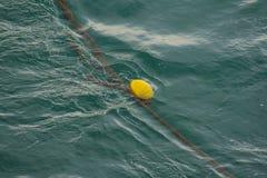 Una boya amarilla que flota en el mar imagenes de archivo