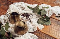Una brocca di latte d'ottone e una ciotola di zucchero d'ottone con i rami dell'edera su un vecchio, piano d'appoggio di legno co fotografia stock libera da diritti
