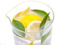 Una brocca piena di bevanda da ghiaccio, dai lobuli del limone giallo succoso fresco e dall'acqua cristallina Fotografie Stock Libere da Diritti