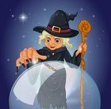 Una bruja con un bastón delante de una bola mágica Foto de archivo libre de regalías