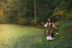 Una bruja joven en bosque fotografía de archivo
