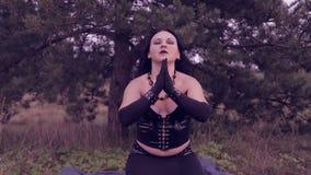 Una bruja joven en negro lanza los guijarros blancos y lee un encanto Víspera de Todos los Santos almacen de metraje de vídeo