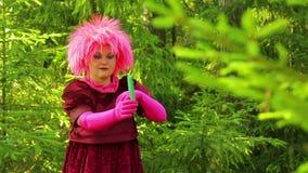 Una bruja joven en un bosque spruce realiza acciones rituales con sus manos sobre una vela ardiente almacen de video