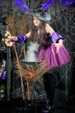 Una bruja joven en un vestido hermoso está cocinando foto de archivo