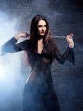 Una bruja joven y atractiva en ropa erótica oscura Imagenes de archivo