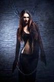 Una bruja joven y atractiva en una alineada negra larga Fotos de archivo libres de regalías