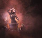 Una bruja morena atractiva que hace el veneno en la mazmorra Imágenes de archivo libres de regalías