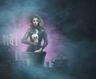 Una bruja morena atractiva que hace el veneno en la mazmorra Imagenes de archivo