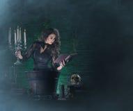 Una bruja morena atractiva que hace el veneno en la mazmorra Fotos de archivo