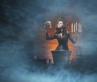 Una bruja morena que hace el veneno en la mazmorra Imagenes de archivo