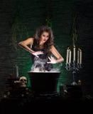 Una bruja triguena atractiva que hace el veneno foto de archivo