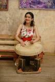 Una bruna attraente sta giocando un tamburino Immagini Stock Libere da Diritti