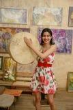 Una bruna attraente sta giocando un tamburino Immagine Stock Libera da Diritti